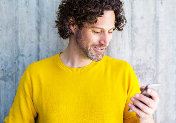 Man in yellow sweater looking at his smartphone