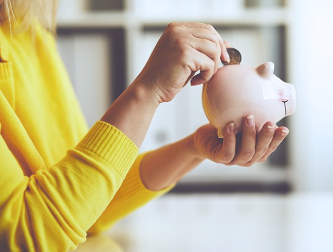 Woman drooping a coin into a piggy bank