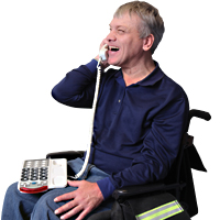 Image of a smiling man sitting in a wheelchair holding the phone headset and the phone is on his lap speaking via Speech to Speech service.