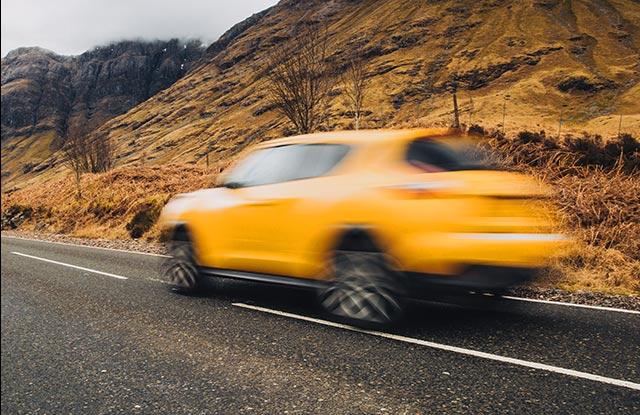Auto amarillo viajando por la carretera