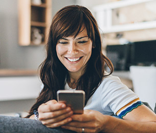 smiling woman sitting on couch looking at her phone