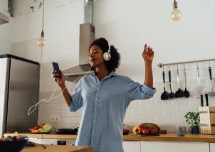 mujer con audífonos bailando en la cocina