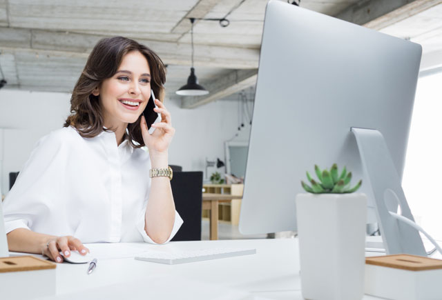 Woman talking on phone in front of a computer